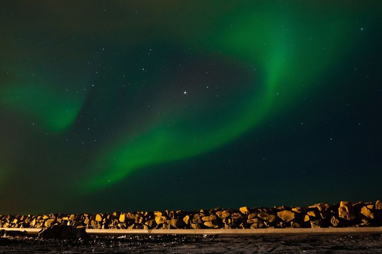 Scenic View Of Aurora Borealis Over Stones On Field At Night