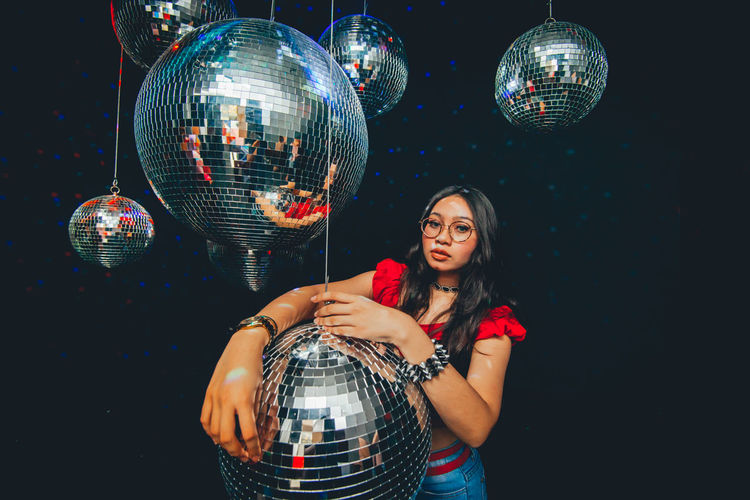 Disco Ball Night One Person Nightlife Young Adult Indoors  Sphere Standing Young Women Black Background Nightclub Illuminated Front View Casual Clothing Holding Shiny Studio Shot Women Reflection Silver Colored