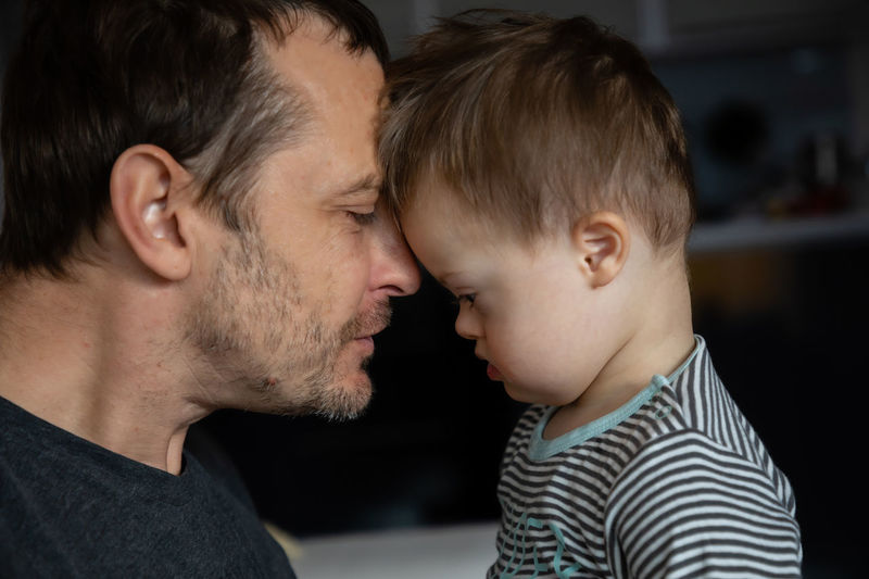 Side view of mid adult man looking at son with down syndrome