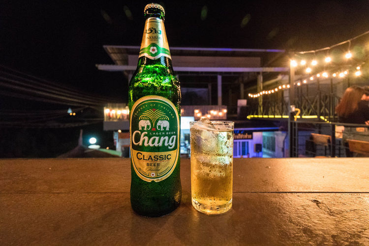 Close-up of beer bottle on table at night