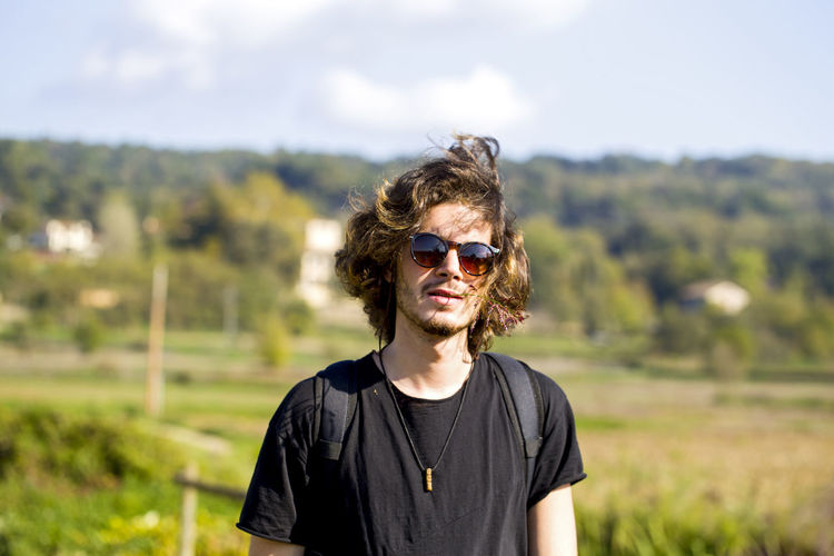 Portrait of young man wearing sunglasses while standing at farm against sky
