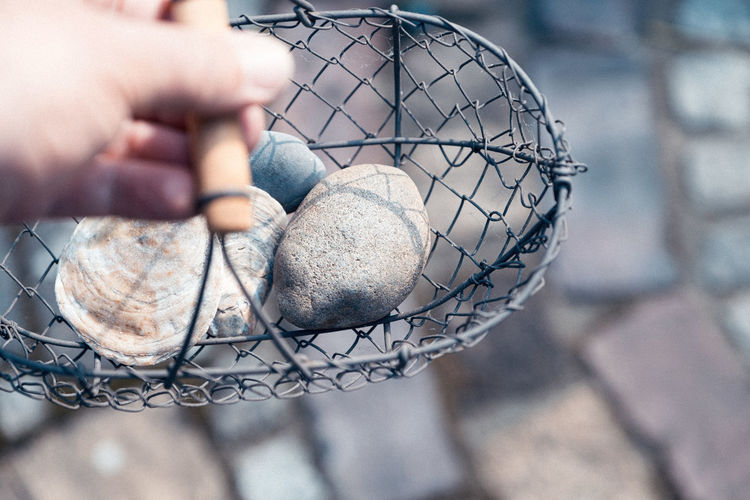 Cropped hand holding stones in metallic basket