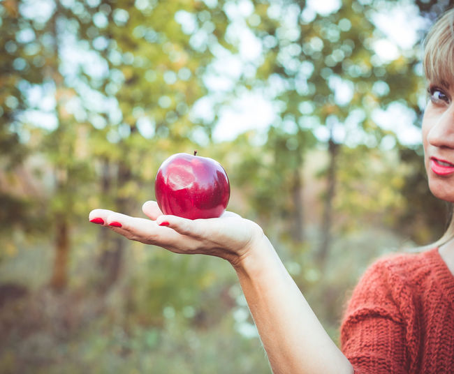 Blond woman holds a large red apple in her hand. Eva style. Seduction. Healthy food Child Plant Hand Food And Drink Close-up Food Headshot Human Hand Lifestyles Leisure Activity Red Real People Outdoors Nature Tree Women Day Focus On Foreground One Person Holding Human Body Part Childhood Apple - Fruit