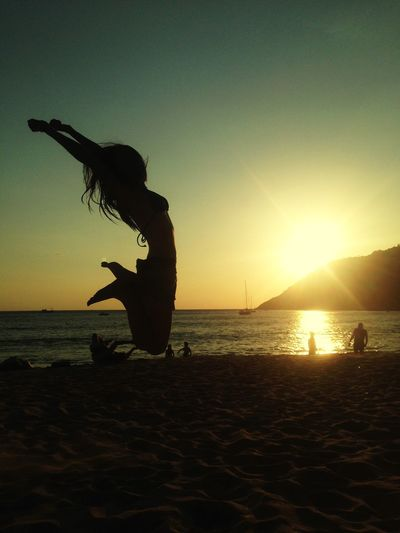 Full Length Of Silhouette Woman Jumping With Arms Raised At Beach During Sunset