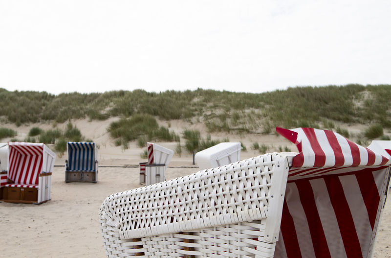The photo shows some beach chairs on the north sea island baltrum with cloudy sky