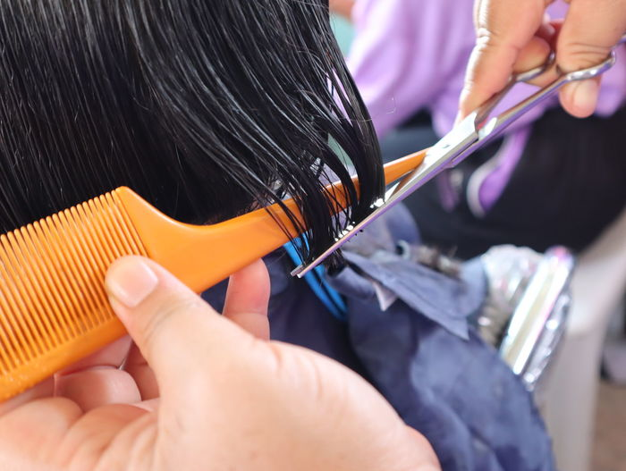 Cropped hands of barber cutting woman hair in salon