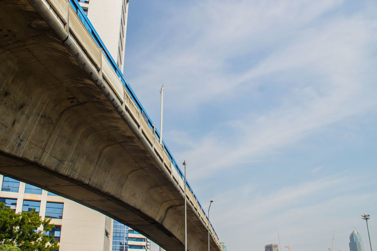 Low angle view of elevated road amidst buildings against sky