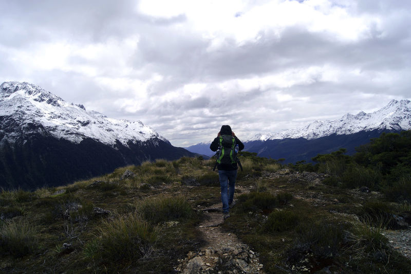 Rear view of a woman on landscape against mountain range
