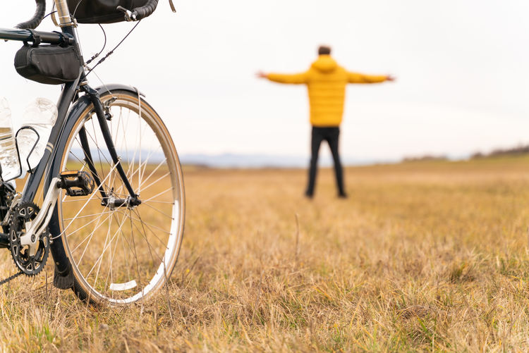 Rear view of man with bicycle standing on field