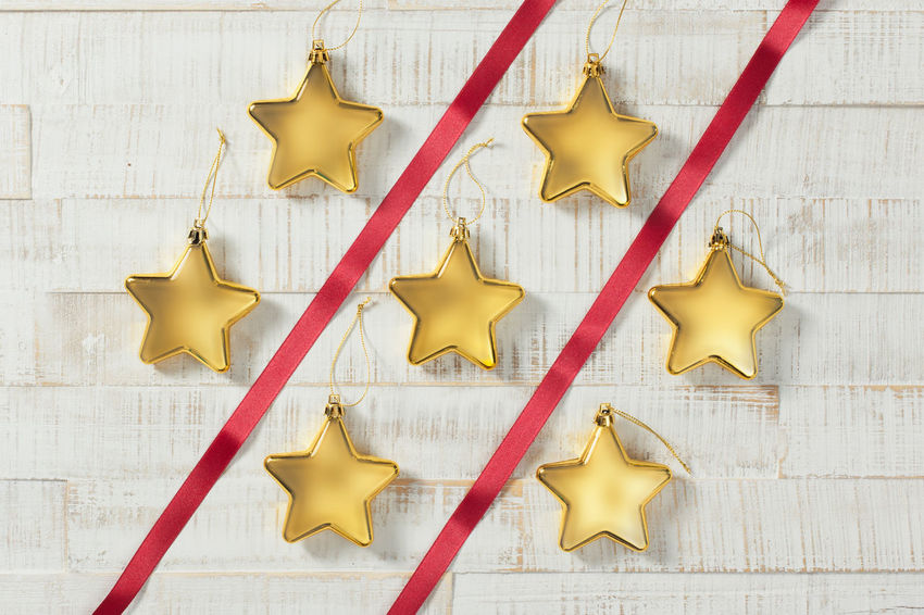 Golden Christmas stars and red ribbons in a pattern on white wood Christmas Close-up Directly Above Gold Colored Indoors  No People Shape Star Shape