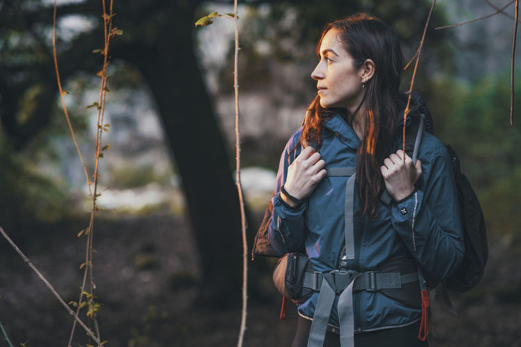 Young woman with backpack looking away while standing in forest
