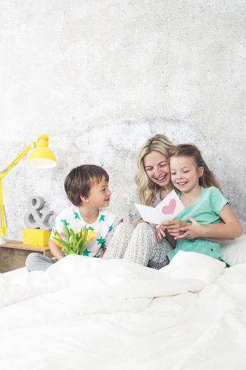 Happy family reading greeting card while sitting on bed at home