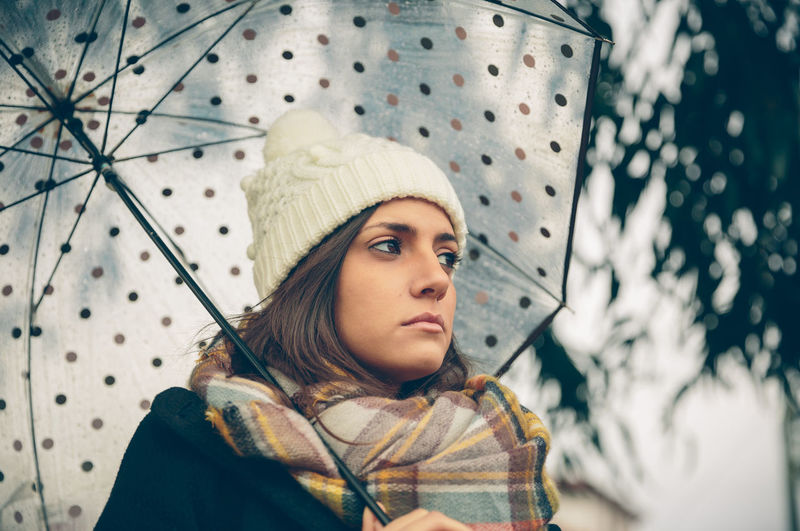 Closeup of young beautiful girl under a umbrella in an autumn rainy day Woman Cold Winter Hat Scarf Horizontal Rain Girl Young Female Outdoors Autumn Fall Real People Caucasian One Person Serious Solitude Pensive Coat Alone Relax Concentration Umbrella Rainy