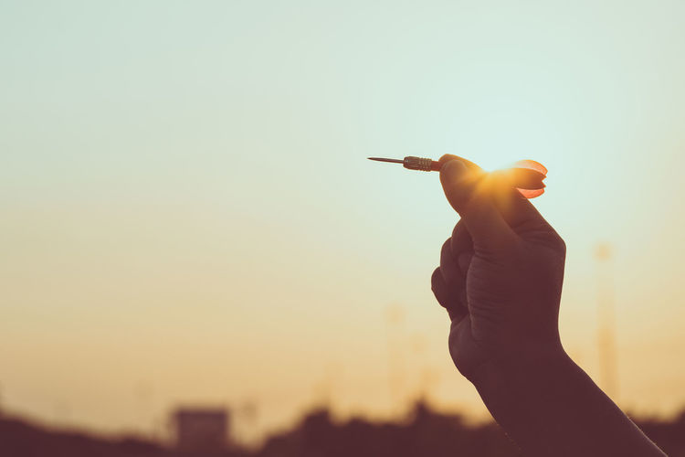 Cropped hand of person holding dart against sky during sunset