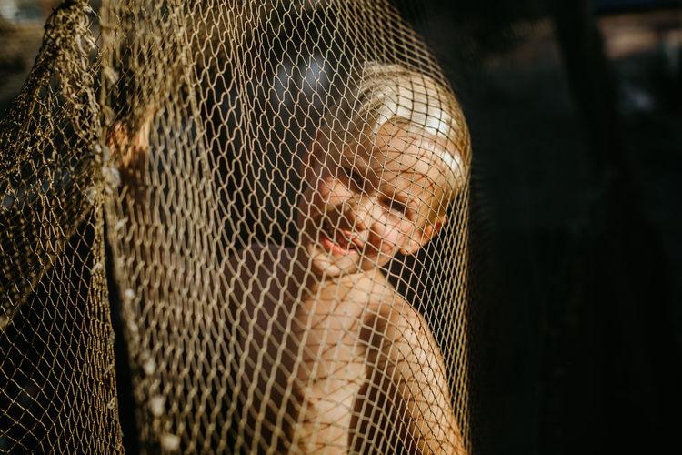 Close-up portrait of cute boy seen through net