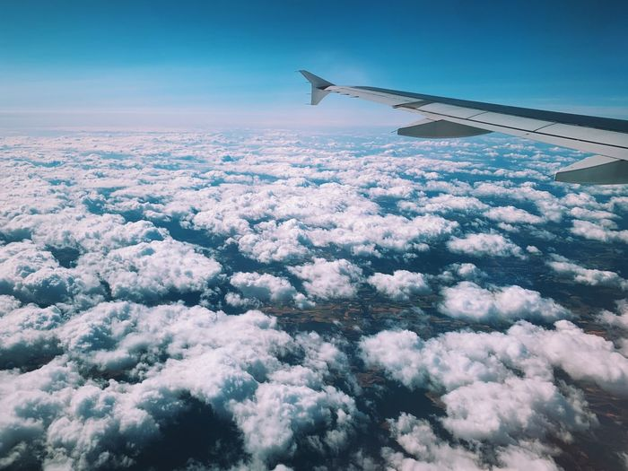 Aircraft wing over cloudscape