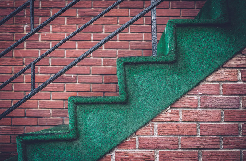 Green staircase against brick wall