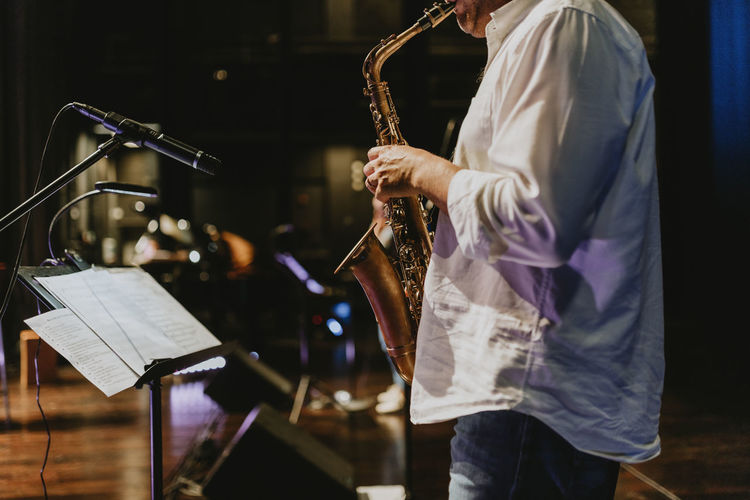 Midsection of playing saxophone at music concert