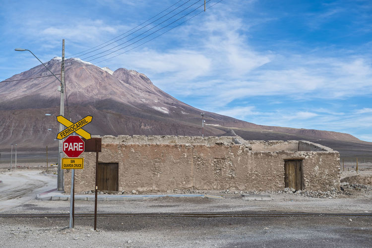 Road sign against mountain and sky