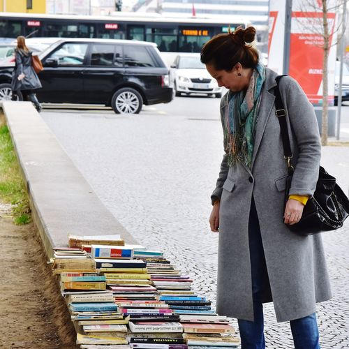 Side view of young woman reading book in city