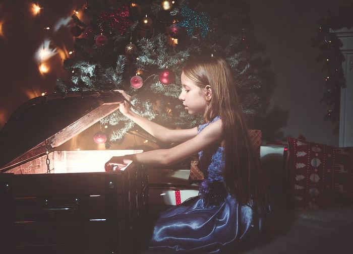 Girl in illuminated christmas tree