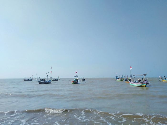 Boats in sea against clear sky