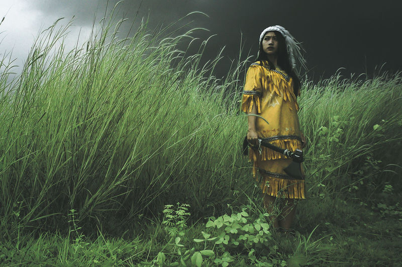 Woman in costume holding axe amidst grass