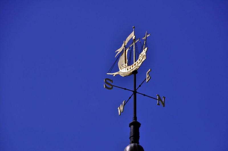 Low Angle View Of Weather Vane With Ship Sculpture Against Clear Blue Sky