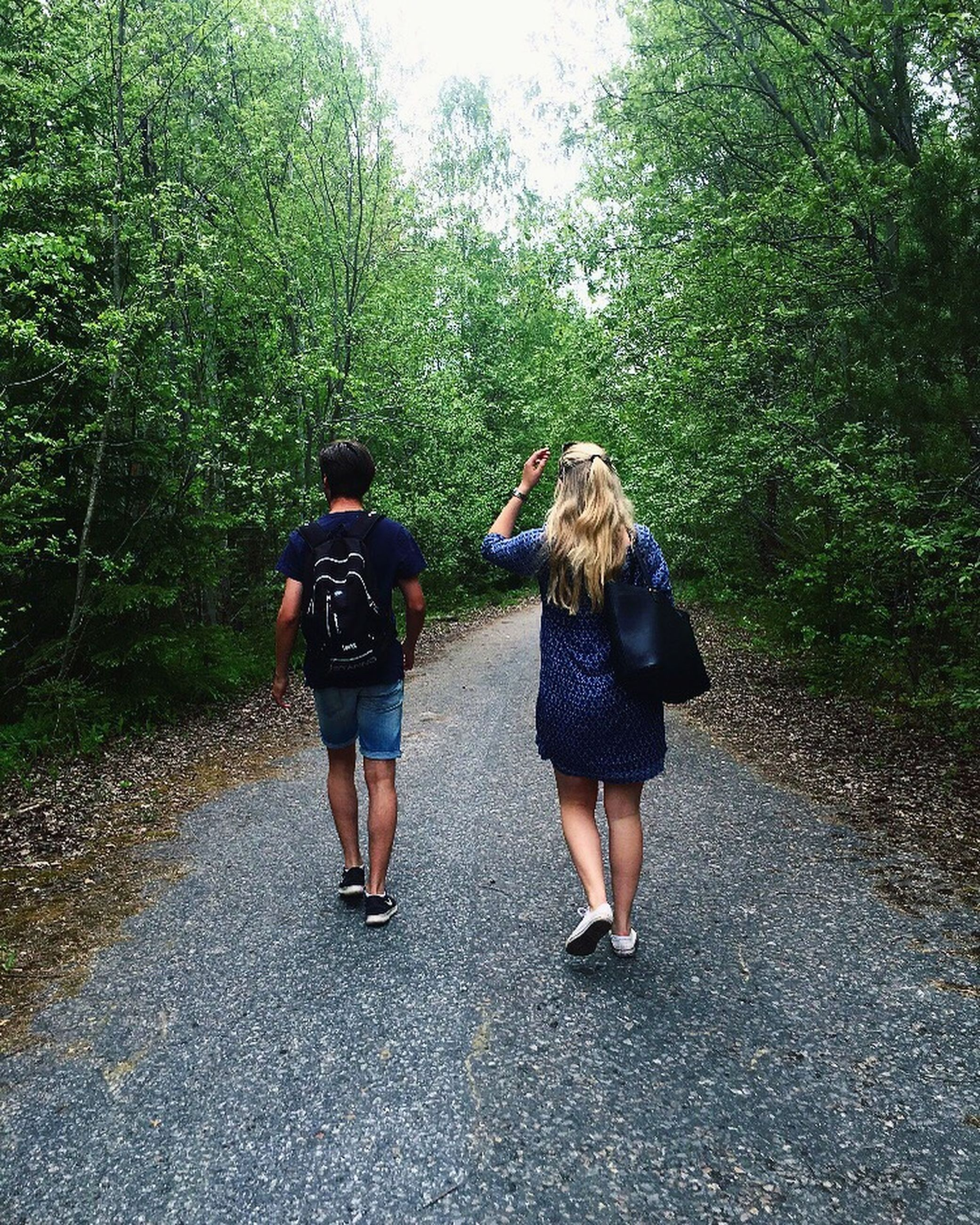 two people, rear view, tree, real people, day, leisure activity, walking, casual clothing, full length, togetherness, outdoors, standing, nature, the way forward, forest, road, lifestyles, women, friendship, young adult, sky