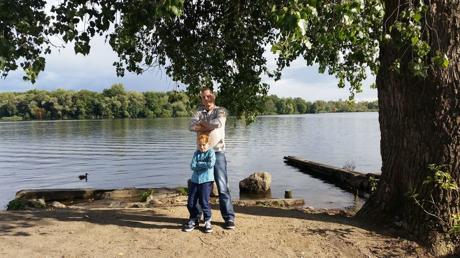 Portrait of father and son with arms crossed standing at lakeshore