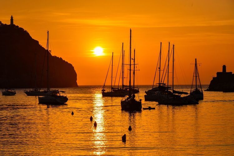 Silhouette boats moored in sea against orange sky during sunset