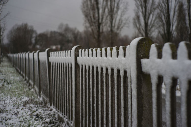 Fence on snow covered landscape