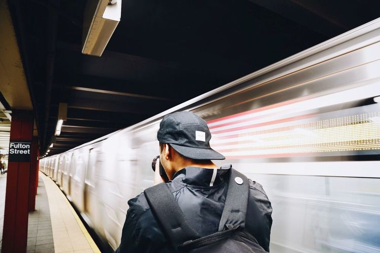 Rear View Of Man Photographing By Blurred Motion Of Train At Subway Station