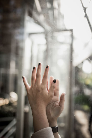 Cropped hand of woman by glass window