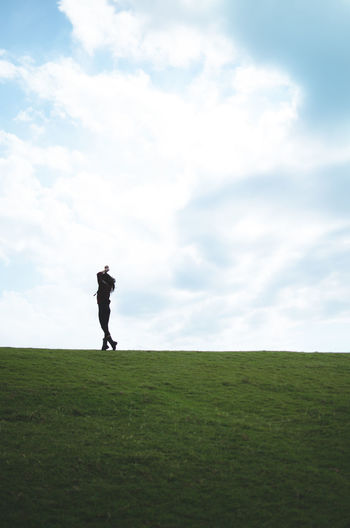 Woman standing on golf course against sky