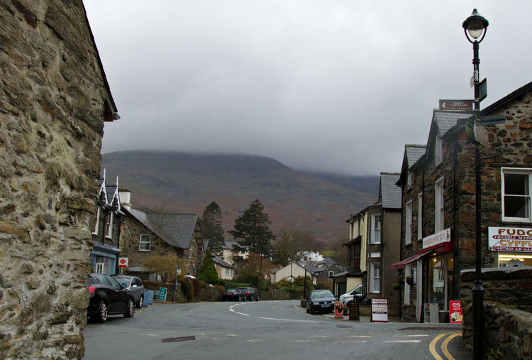A beautiful small village which occupies the site of Gelert's grave, the dog of 13th century Prince of North Wales, Llywelyn. Llywelyn went hunting on a particular day without his dog. When Llywelyn returned back to his palace, in Beddgelert, his dog was happy to see him but he found his dog stained with blood and his son was missing from his cot and bloodstained bedclothes and floor. Llywelyn grabbed his sword and plunged it into the side of his dog thinking his dog had killed his son. As the dog yelled Llywelyn heard a cry of a baby. It was his son unharmed. Llywelyn also found the body of a wolf lying nearby which Gelert had killed to protect the prince's son. In remorse of killing his faithful dog the Prince was said to have never smiled again. Village City Tree Fog Architecture Sky Vehicle