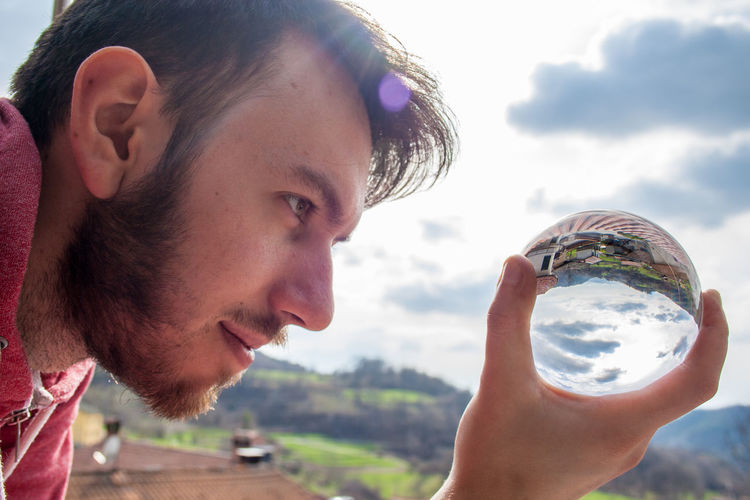 Close-Up Of Young Man Holding Crystal Ball