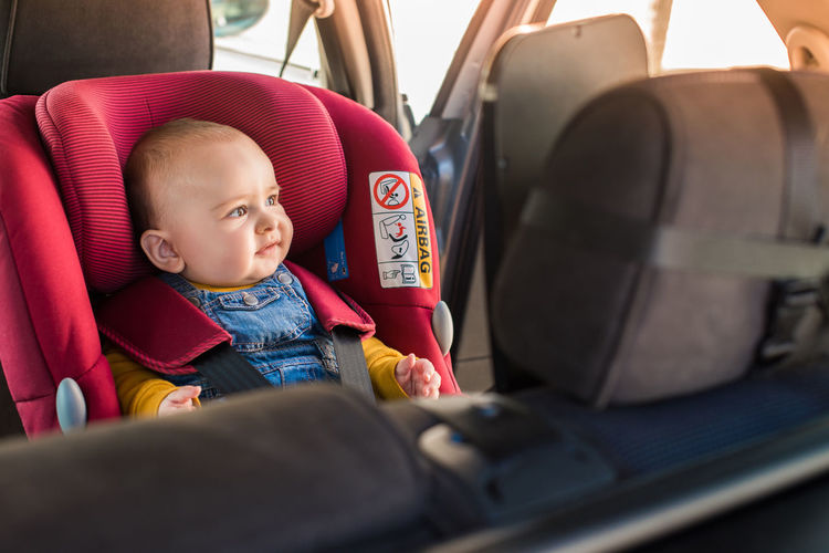 Cute baby girl sitting in car
