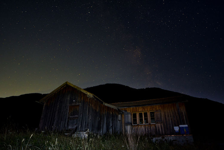Abandoned house on field against sky at night