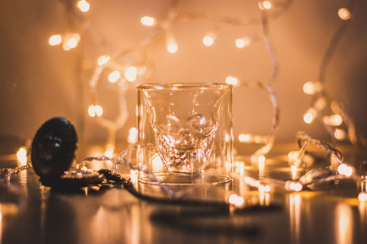 Close-up of glass with illuminated string lights on table