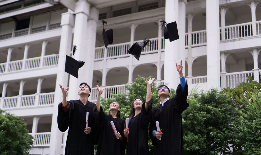 Achievement Architecture Arms Raised Building Exterior Built Structure Celebration Day Emotion Graduation Graduation Gown Group Of People Happiness Human Arm Men Mortarboard Outdoors People Positive Emotion Real People Standing Success University Student Women Young Adult