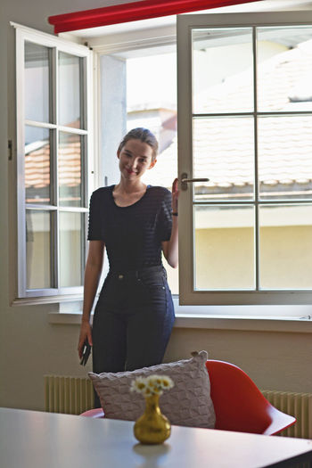 Portrait of young woman standing against window at home