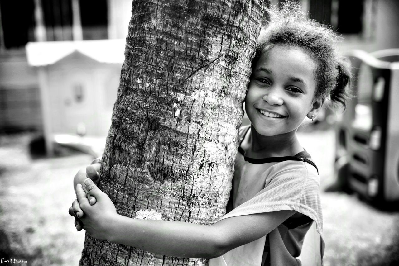 childhood, tree trunk, focus on foreground, tree, looking at camera, real people, smiling, happiness, elementary age, portrait, one person, girls, outdoors, day, cute, casual clothing, holding, leisure activity, standing, child, playing, boys, lifestyles, close-up, nature