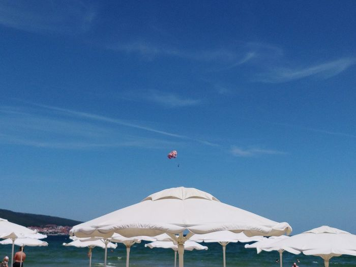 White umbrella on beach against blue sky
