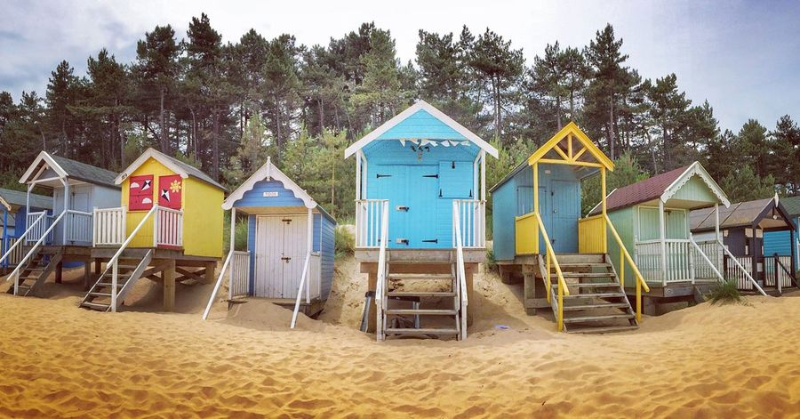A panoramic view of the colourful, wooden beach huts on the sandy beach of Wells Next The Sea in Norfolk, U.K. Sand Beach Multi Colored Built Structure Day Tree Outdoors No People Sky Vacations Sandy Rows Wells-next-the-Sea Summertime Huts Hut Stilts Beach Hut Summer Vacations Norfolk Travel Destinations Beach Huts Travel Vacation
