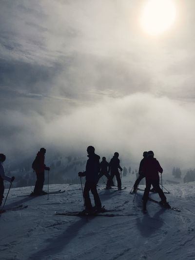 Silhouette skiers on snowcapped mountain against cloudy sky