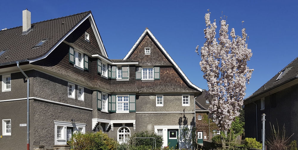 Residential houses on the Margarethenhöhe Cherry Blossoms Margarethenhöhe Architecture Blue Building Building Exterior Built Structure Cherry Tree Clapboard Clear Sky Growth House No People Old House Plant Romantic House Shingle Sky Spring Springtime Tree Window