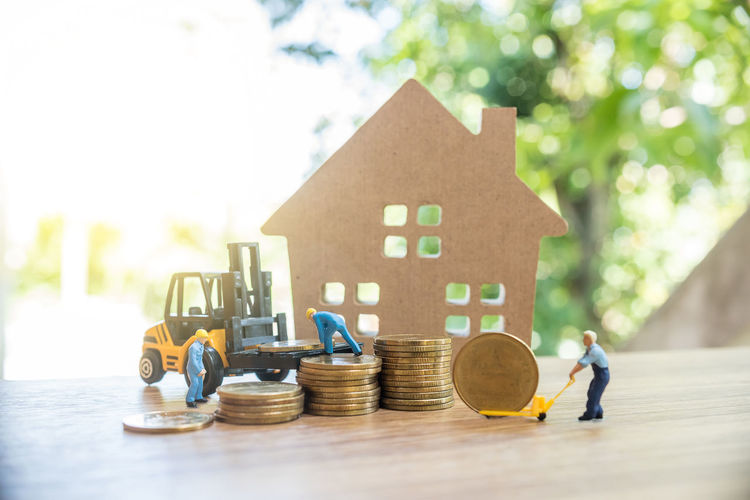 Close-up of figurines with toy forklift with coins and house on table