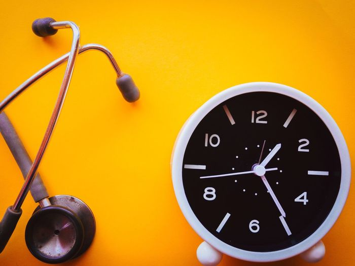 Stethoscope  Yellow No People Clock Time Wall - Building Feature Close-up Instrument Of Time Number Indoors  Orange Color Clock Hand Shape Geometric Shape Studio Shot Black Color Yellow Background Minute Hand Circle Multi Colored Wall Clock