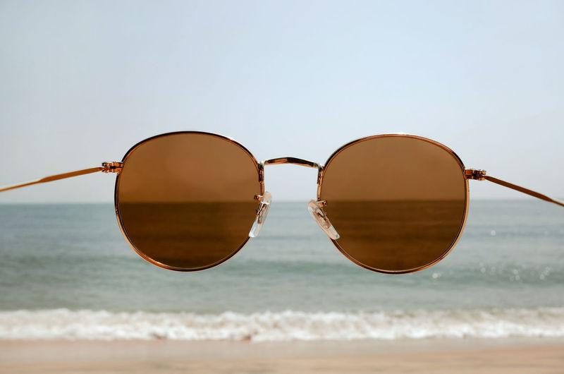 Sunglasses on beach against clear sky